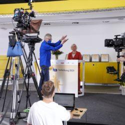 Making-of 3. Bühne mit Kamerateam und Rednerin - Filmklappe für den Drehbeginn.