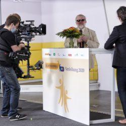 Making-of 9. Laudatorin und Gewinner im Gespräch am Stehtisch. Davor Mann mit Filmkamera.